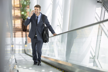Businessman smiling at the office building escalator