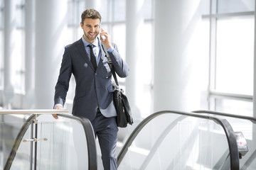 Businessman on the phone smiling at the escalator
