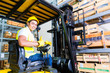 Asian fork lift truck driver lifting pallet in storage - 69907390