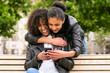 canvas print picture - Beste Freunde chatten mit Smartphone auf Parkbank