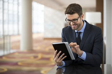 Smiley businessman with glasses using tablet at the hotel lobby