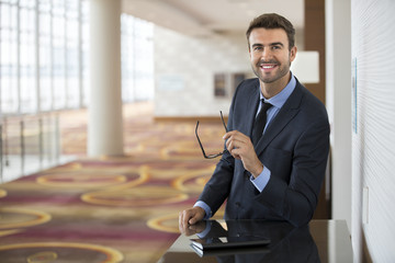 Happy businessman with glasses using tablet at the hotel lobby