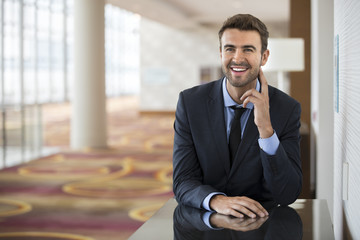 Portrait of happy businessman at hotel lobby