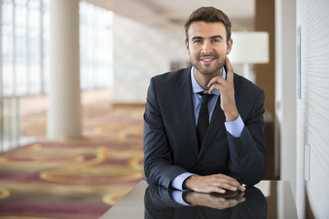 Portrait of happy businessman at office lobby