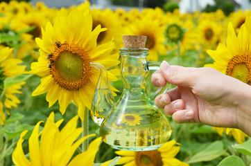 Bottle of oil against sunflowers