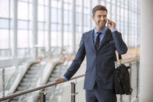 Businessman talking on mobile phone in office lobby - 69907986