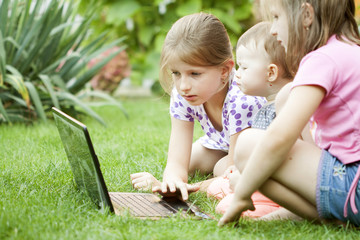 Children using laptop in the meadow