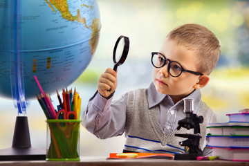 Boy looking through magnifying glass at globe