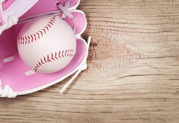Baseball. Ball in Pink Female Glove over wood background