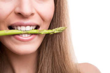 Girl biting asparagus