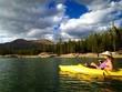 Female kayaker with dog kayaking on Lake.