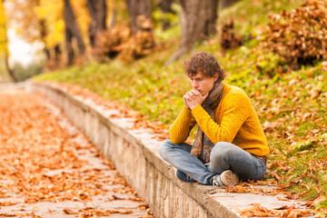sad curly man siting outdoor
