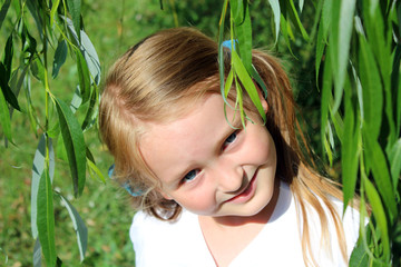 girl smiling besides the leaves of willow