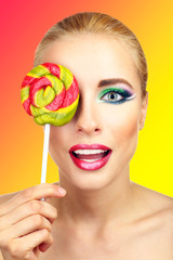 Beautiful woman with colorful lollipop, on bright background