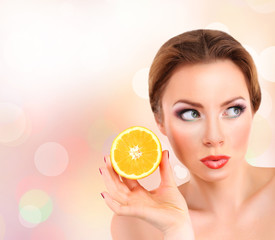 Beautiful young woman with bright make-up, holding orange