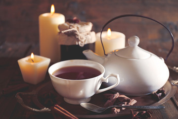 Composition with tea in cup and teapot and candles