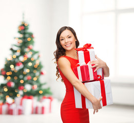 smiling woman in red dress with many gift boxes