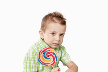 Pensive little boy con lollipop