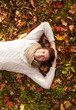 smiling young man lying on ground in autumn park