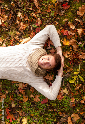 canvas print picture smiling young man lying on ground in autumn park