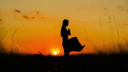 Silhouette of a Young Girl Doing Yoga At Sunset