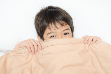 Little boy lay on bed with blanket cover half face
