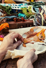 woman's hand in the process of needlework sewing tools