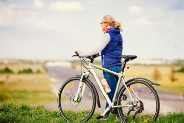 Girl with bike on hill