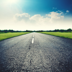 Asphalt road under wide blue skies, abstract travel backgrounds