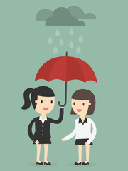 business woman with umbrella protects another woman from rain