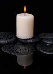 spa concept of candle on zen stones with drop in reflection wate