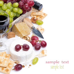 cheeses, red and green grapes, crackers and wine, isolated
