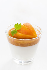 dessert with cream and apricot jelly in a glass, close-up
