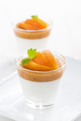 dessert with cream and apricot jelly in glasses on white plate