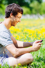 Guy messaging outdoors