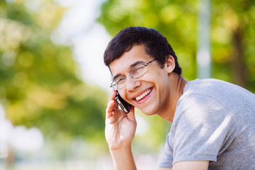 Guy talking on phone in park