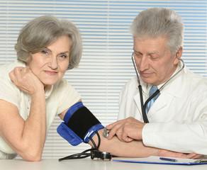 Elderly doctor measuring blood pressure