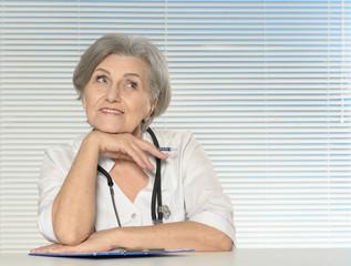 Thinking senior doctor woman