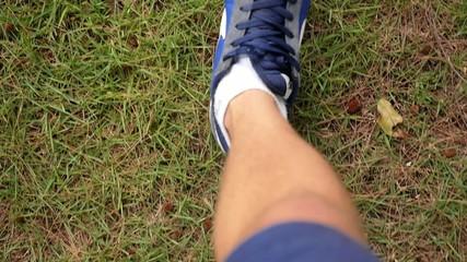 Legs of Walking Man in Sport Shoes on Grass. Slow Motion.