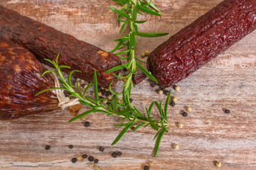 smoked salami on wooden table with rosemary