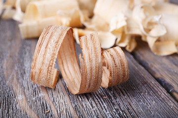 Wood shavings on grey wooden background closeup
