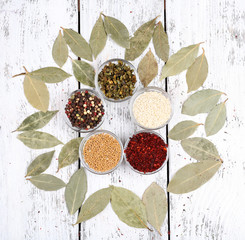Spices with bay leaves on wooden background