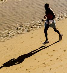 Hombre corriendo por la orilla de la playa