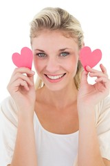 Smiling young woman holding pink hearts