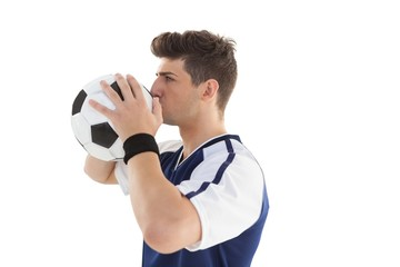 Side view of a football player kissing ball