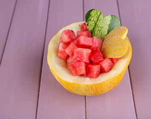 Slices of watermelon in melon bowl on wooden background