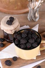 Sweet blackberries in color mug and tasty jam