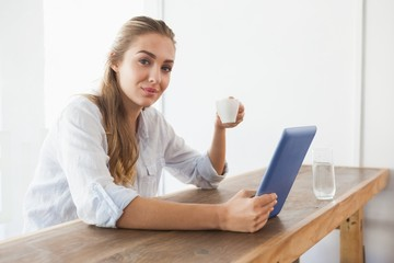 Pretty blonde having coffee while using tablet