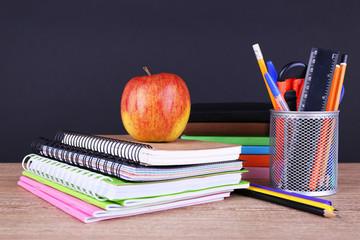 School supplies on table on dark background