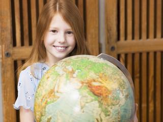 Mädchen (4-7) hält Globus,lächelnd,Porträt
